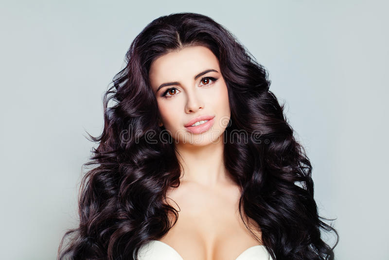 Den härliga kvinnamodellen med långt skinande krabbt hår och gör perfekt hud Nätt modell med den lockiga frisyren royaltyfri foto