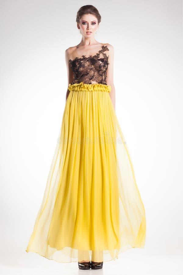 Den härliga kvinnamodellen som poserar i lång gul klänning med svart, snör åt fotografering för bildbyråer