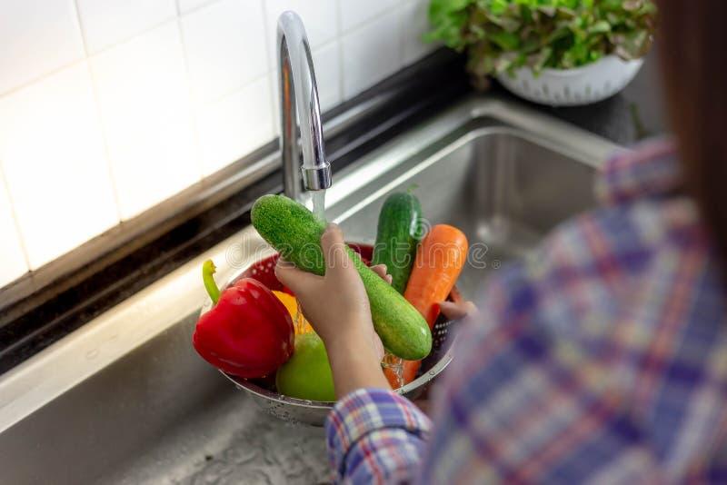 Den härliga kvinnan är göra ren och tvätta gurkan och grönsaker fotografering för bildbyråer