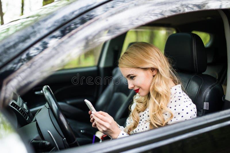 Den härliga kvinnan är sitta och köra en bil som rymmer en mobiltelefon och en messaging royaltyfria foton