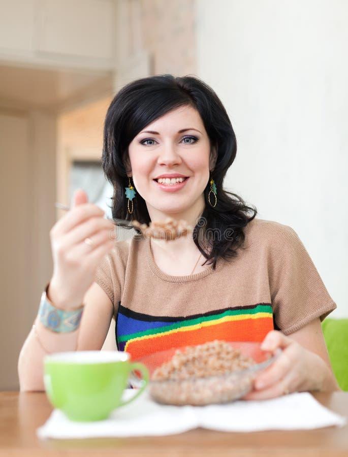 Den härliga kvinnan äter bovete royaltyfri foto