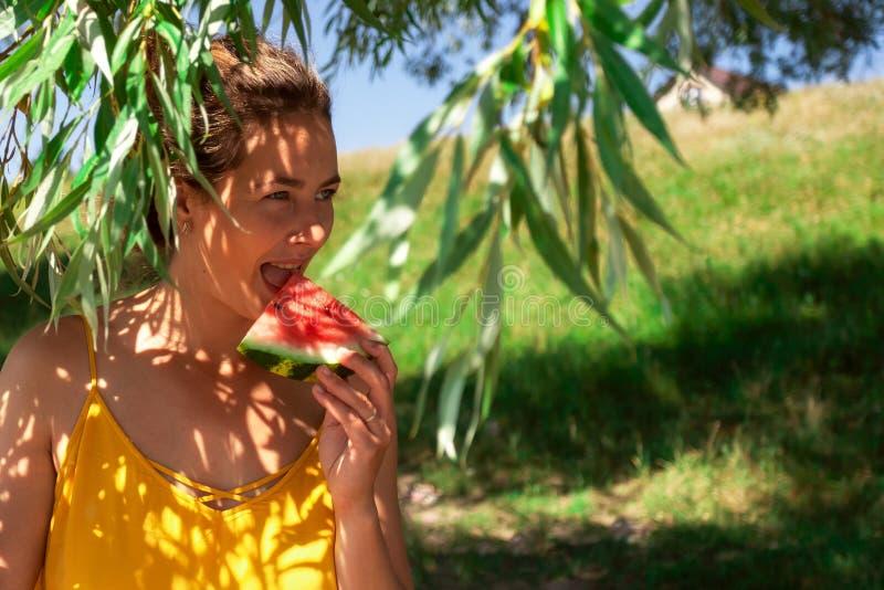 den härliga kvinnan äter waretmelon arkivbild