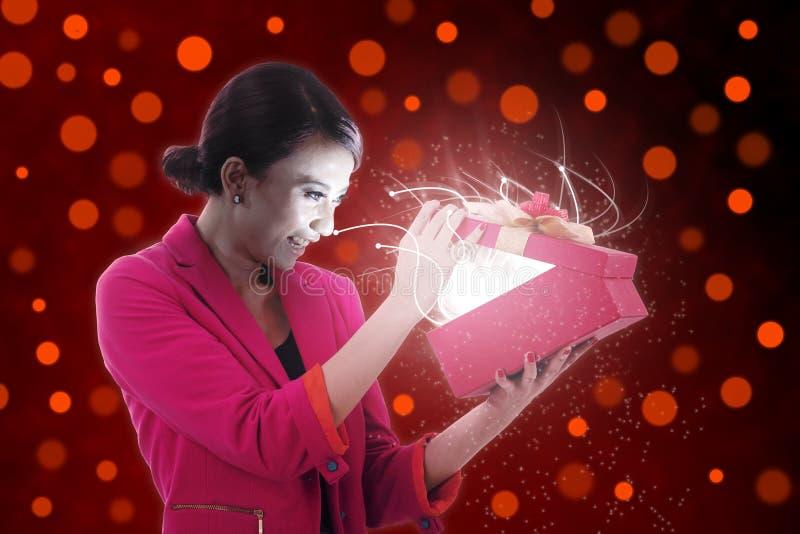 Den härliga kvinnan öppnar en present arkivfoto