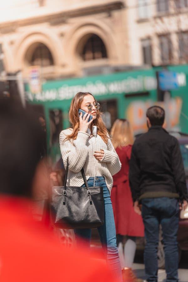 Den härliga kvinnan använder smartphonen, medan gå arkivbild