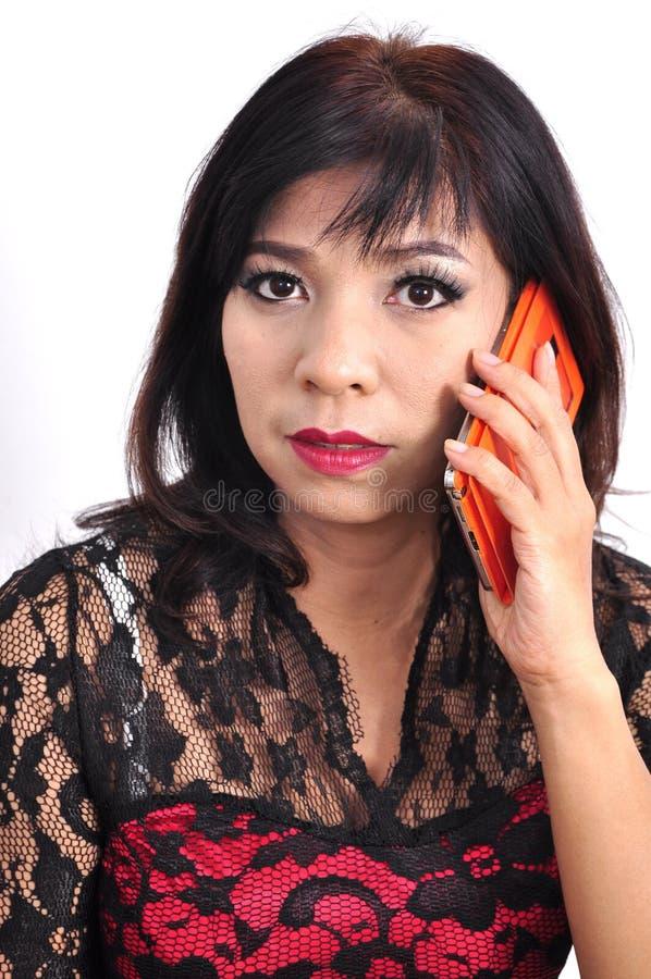 Den härliga kvinnan använder smartphonen som vänder mot kameran arkivfoton