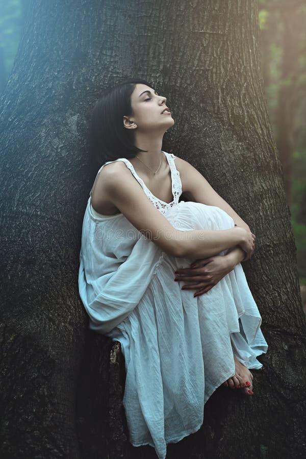 Den härliga kvinnan bland mörkt träd rotar royaltyfri fotografi