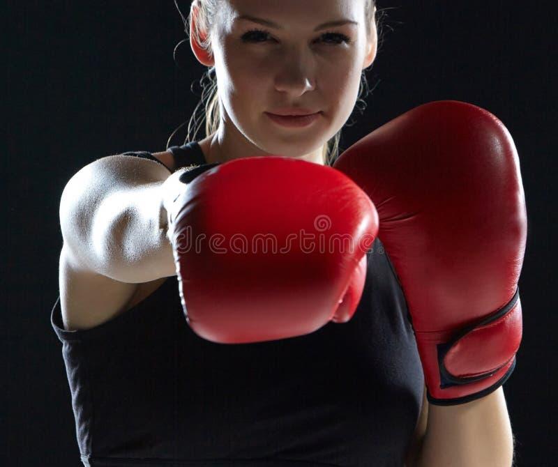 Den härliga kvinnan boxas på grå bakgrund royaltyfri foto
