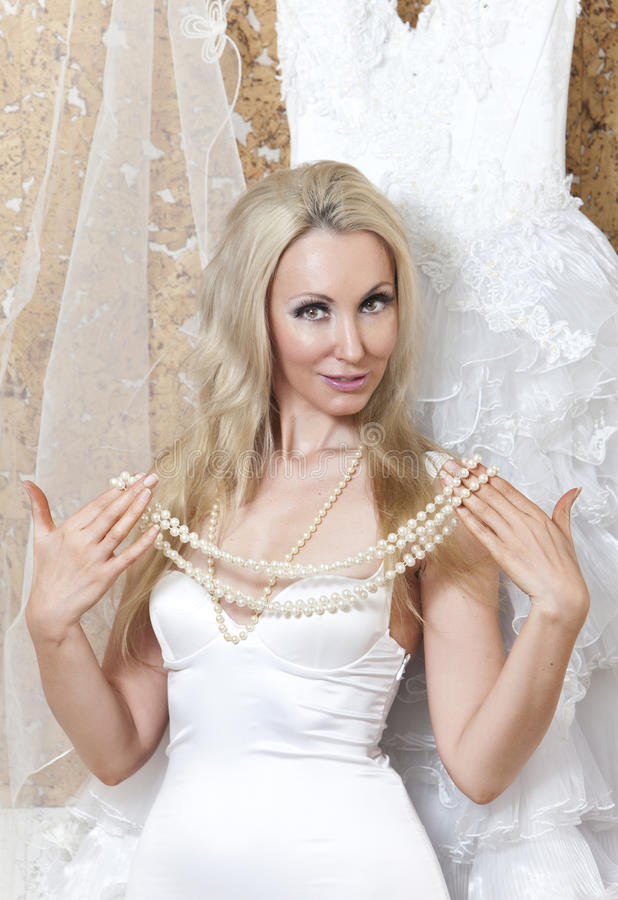Den härliga kvinnan, bruden, nära bröllopsklänningen drömmer om bröllop royaltyfri foto