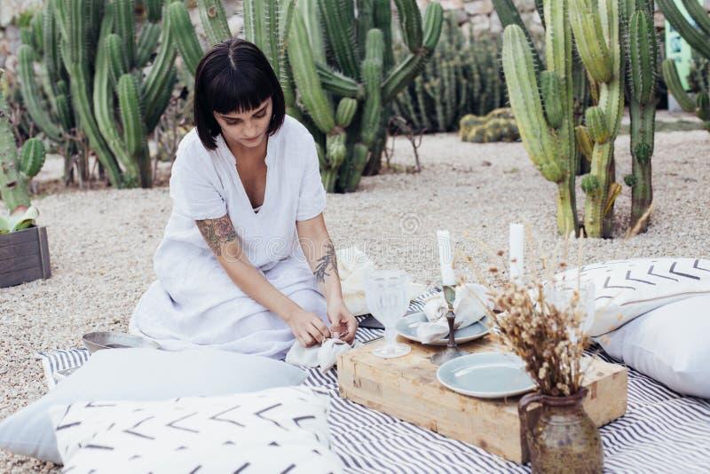 Den härliga kvinnan dekorerar matställetabellen royaltyfria foton