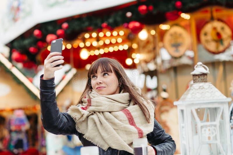 Den härliga kvinnan dricker funderat vin och gör ett selfy på mobil p arkivfoto