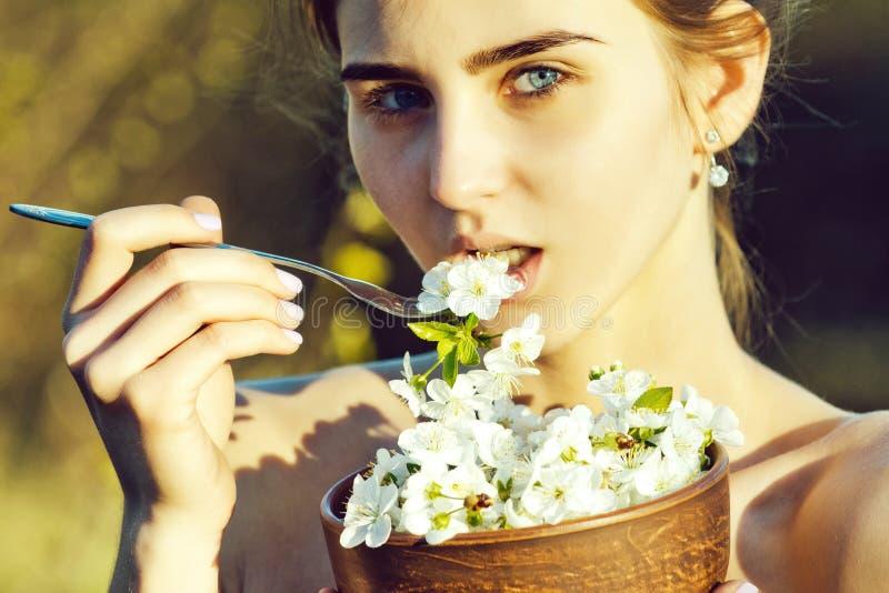 Den härliga kvinnan eller den gulliga flickan som äter blommor, fjädrar den körsbärsröda blomningen arkivfoto