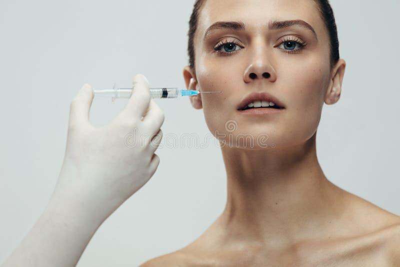 Den härliga kvinnan får injektionen i hennes framsida royaltyfria bilder