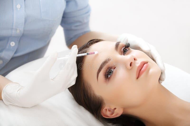 Den härliga kvinnan får injektionen i hennes framsida. Kosmetisk kirurgi royaltyfria bilder
