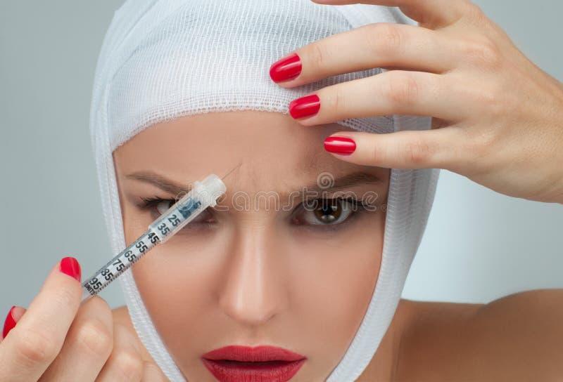 Den härliga kvinnan får injektionen med den förband framsidan Skönhet-, mode- och plastikkirurgibegrepp fotografering för bildbyråer