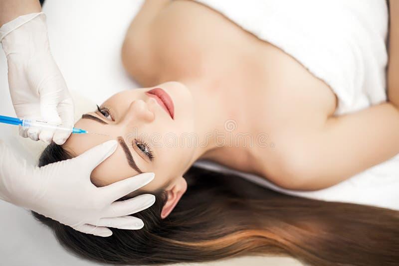 Den härliga kvinnan får injektioner cosmetology Härlig le flicka royaltyfria foton