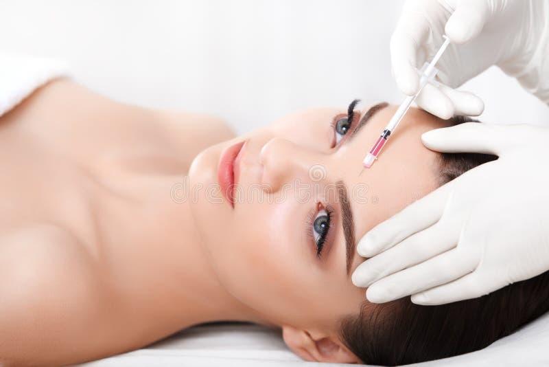 Den härliga kvinnan får injektioner cosmetology Härlig le flicka royaltyfri bild