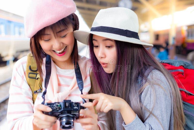 Den härliga kvinnan får spännande, när den turist- kvinnan att se det underbara fotoet på kameran och ordstäven överraskar som gö arkivbilder