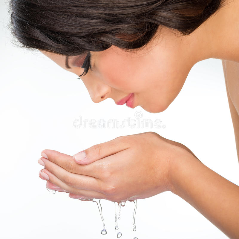 Den härliga kvinnan gör ren hennes framsida med vatten royaltyfri foto