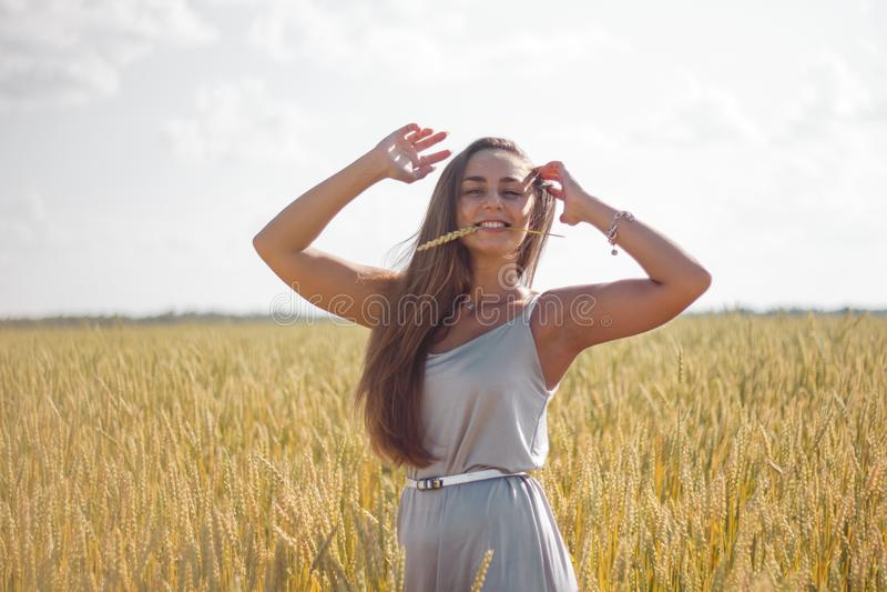 Den härliga kvinnan garvade för lång brun anseende för klänning hårsilver för hud siden- på ett fält fotografering för bildbyråer
