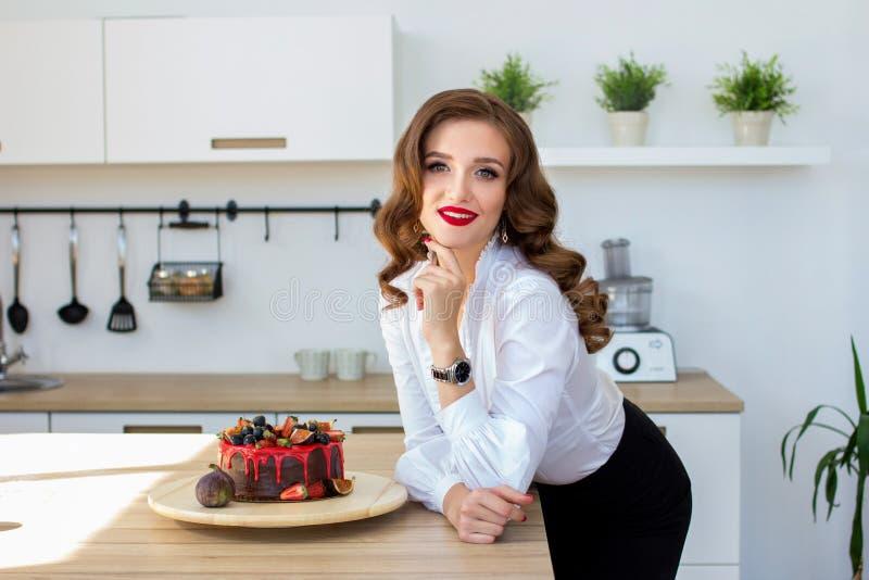 Den härliga kvinnan har gjort kakan i kök arkivbild