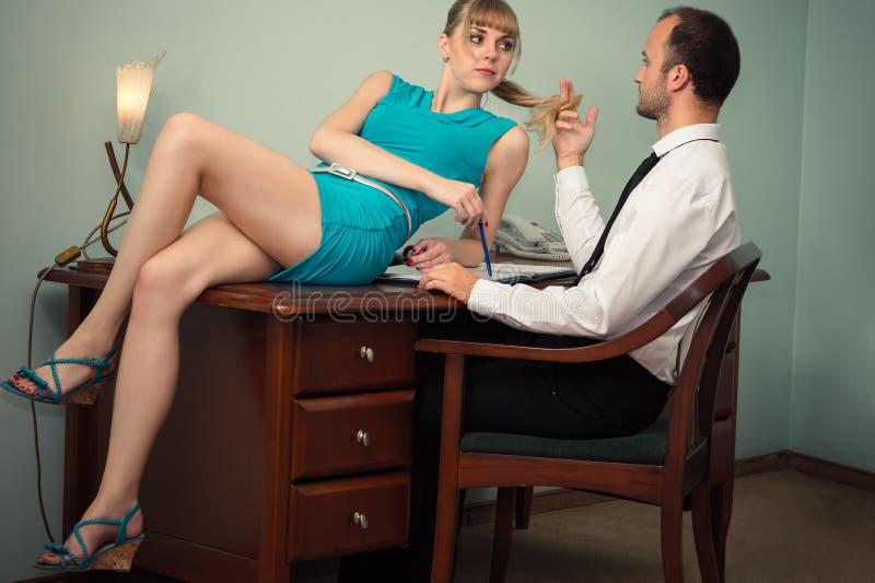 Den härliga kvinnan i blått klär ligga på tabellen framme framstickandet fotografering för bildbyråer