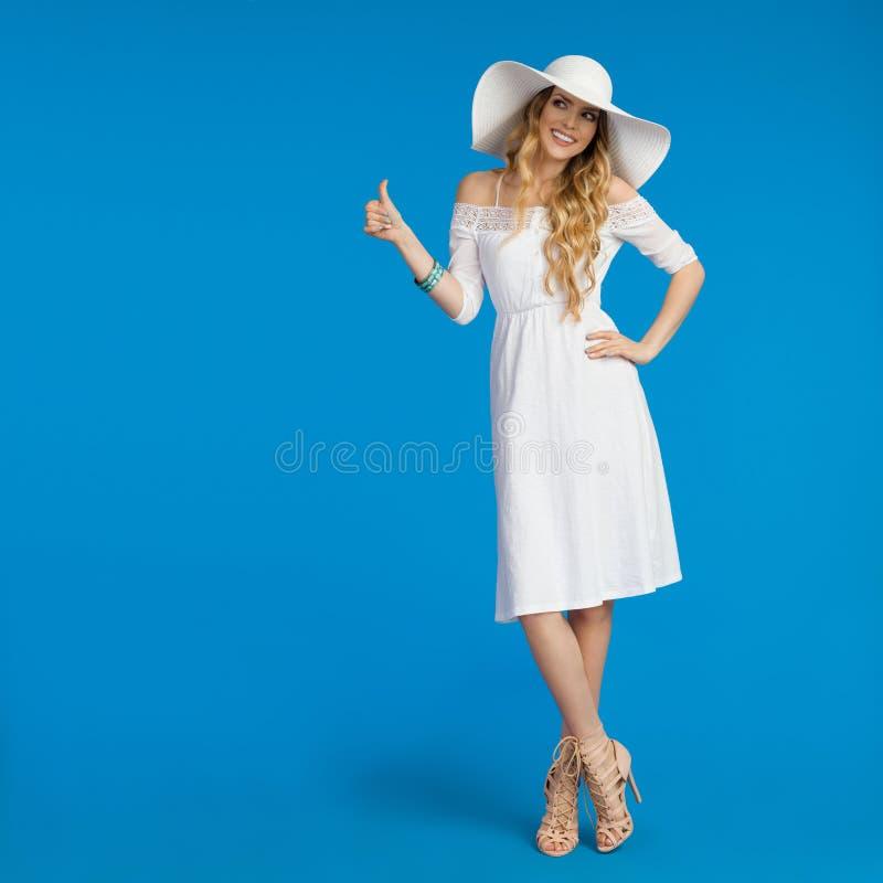 Den härliga kvinnan i den vita klänning- och solhatten visar upp tummen royaltyfri bild