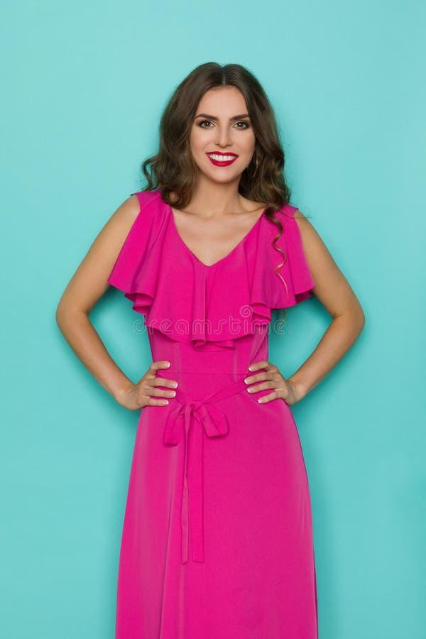 Den härliga kvinnan i elegant rosa klänning poserar med händer på höft arkivfoto