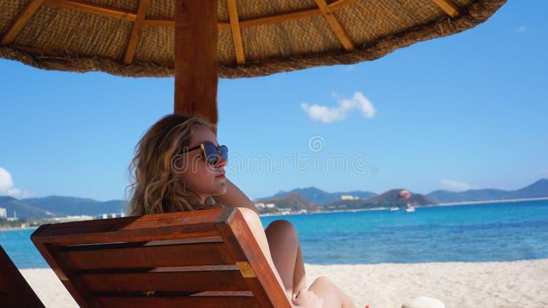 Den härliga kvinnan i en bikini tycker om den tropiska solen för ett solbränt på en sunchair arkivbilder