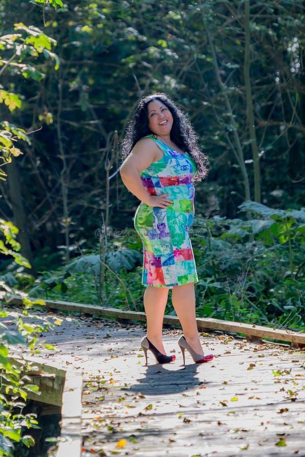 Den härliga kvinnan i en blå klänning med mångfärgad garnering på en stenbana i parkerar fotografering för bildbyråer