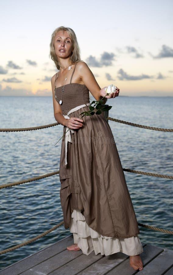 Den härliga kvinnan i en lång klänning på en träplattform över havet fotografering för bildbyråer