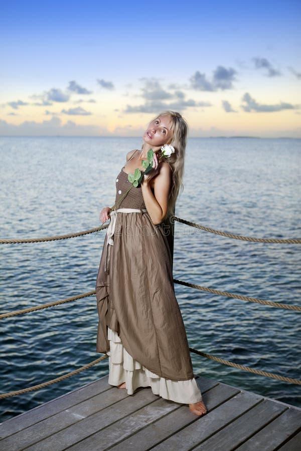 Den härliga kvinnan i en lång klänning på en träplattform över havet arkivbilder