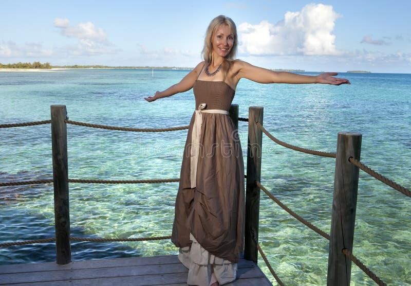 Den härliga kvinnan i en lång klänning på en träplattform över havet royaltyfri fotografi