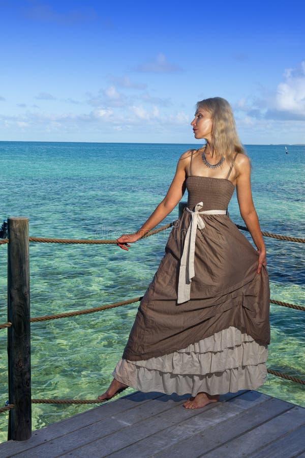 Den härliga kvinnan i en lång klänning på en träplattform över havet arkivbild