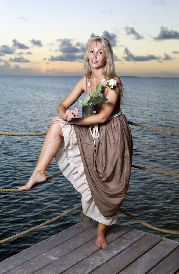Den härliga kvinnan i en lång klänning på en träplattform över havet arkivfoton