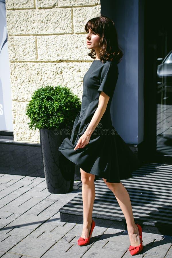 Den härliga kvinnan i en mörk stilfull klänning strosar along Stående av en trendig flicka royaltyfri fotografi
