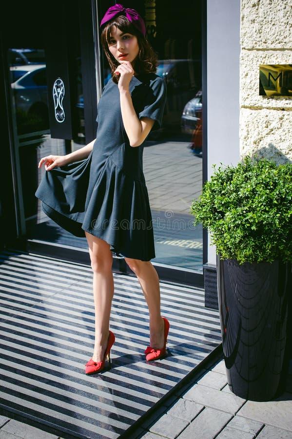 Den härliga kvinnan i en mörk stilfull klänning strosar along Stående av en trendig flicka fotografering för bildbyråer