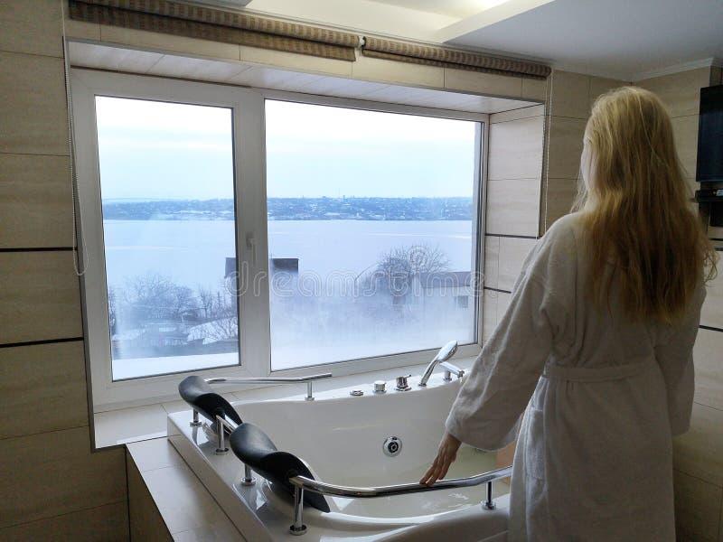 Den härliga kvinnan i ett varmt badar Bubbelpool i hotellet, panoramautsikt från fönstret i badrummet royaltyfria foton
