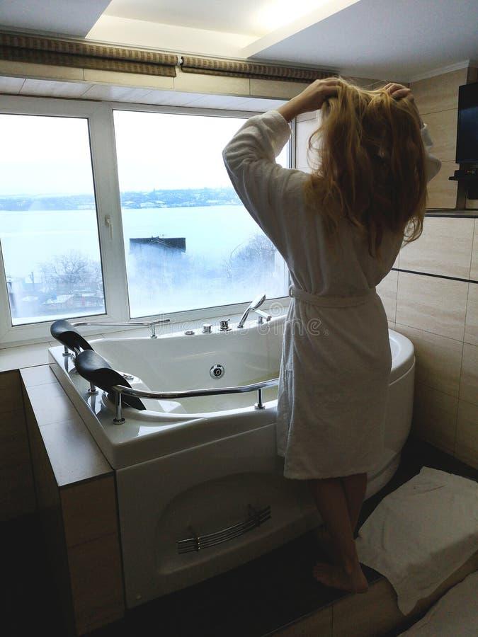 Den härliga kvinnan i ett varmt badar Bubbelpool i hotellet, panoramautsikt från fönstret i badrummet royaltyfria bilder