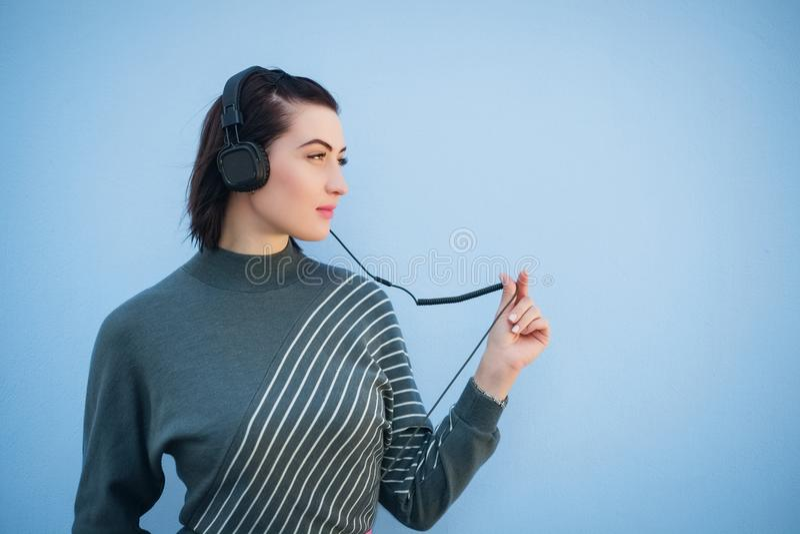 Den härliga kvinnan i hörlurar på blå väggbakgrund i grå färger klär royaltyfri fotografi