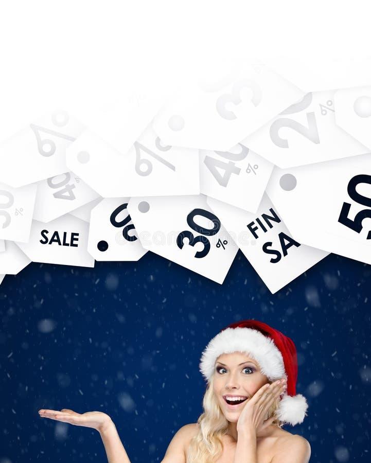 Den härliga kvinnan i jullockgester gömma i handflatan upp erbjudandet av dagen arkivfoton