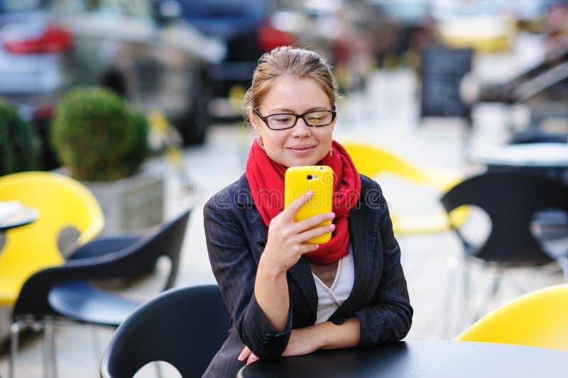 Den härliga kvinnan i kafé ser telefonen royaltyfri foto