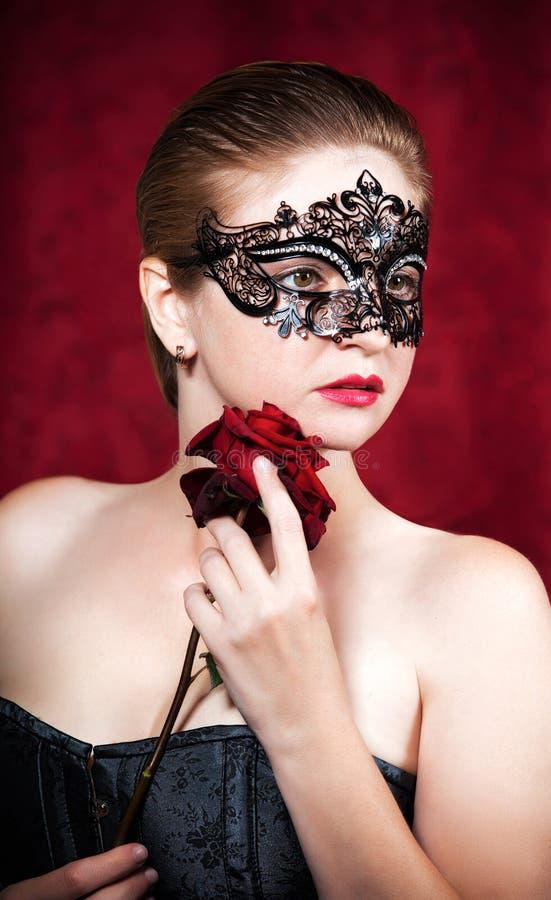 Den härliga kvinnan i karnevalmaskering med red steg royaltyfri bild