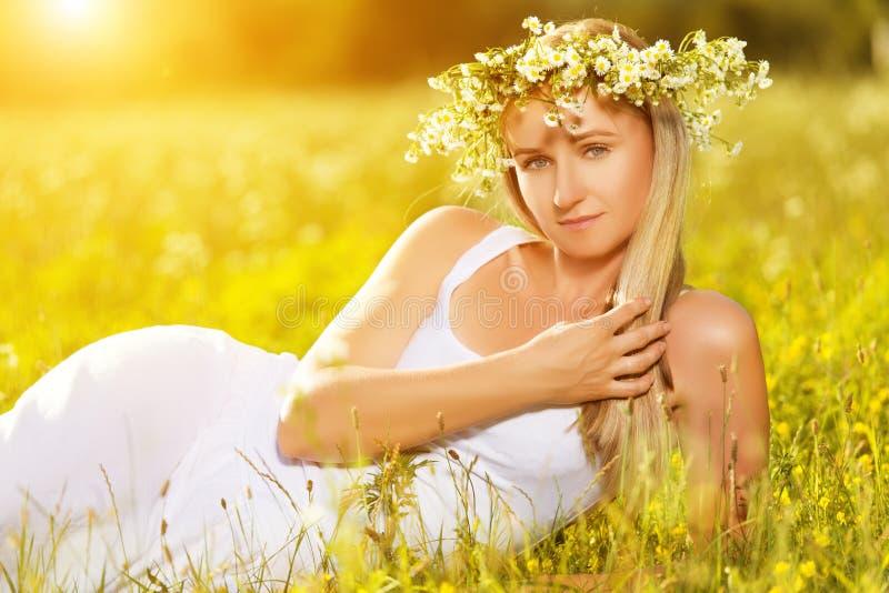 Den härliga kvinnan i krans av blommor ligger i det gröna gräset ut royaltyfria foton