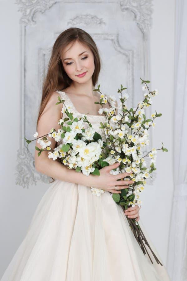 Den härliga kvinnan i lång klänning rymmer vita blommor arkivbilder