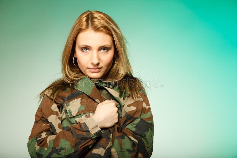 Den härliga kvinnan i militär beklär ståenden arkivfoto