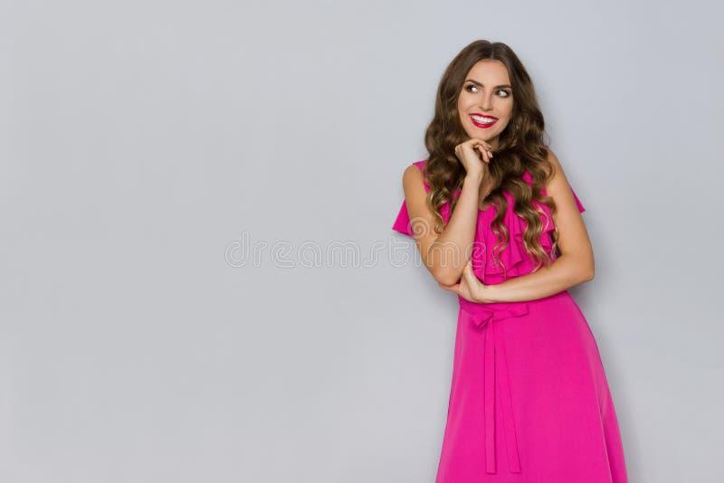Den härliga kvinnan i rosa klänning rymmer handen på hakan, att se bort och att le royaltyfri bild