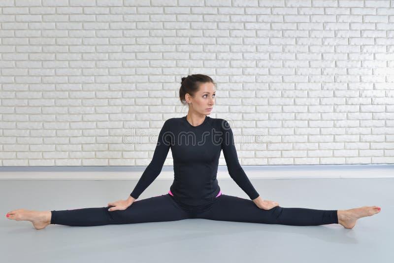 Den härliga kvinnan i sportswear som övar på konditionstudion som utför tvinnar sammanträde på golvet royaltyfri fotografi