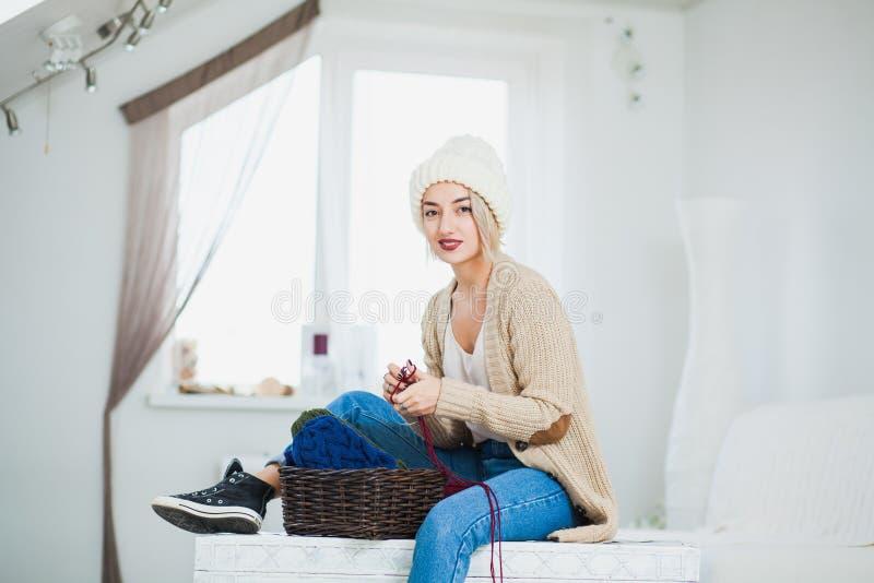 Den härliga kvinnan i stor vit stucken hatt sitter inomhus på bröstkorg med korggarn arkivfoton
