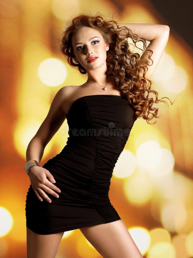 Den härliga kvinnan i svart klänning poserar. fotografering för bildbyråer