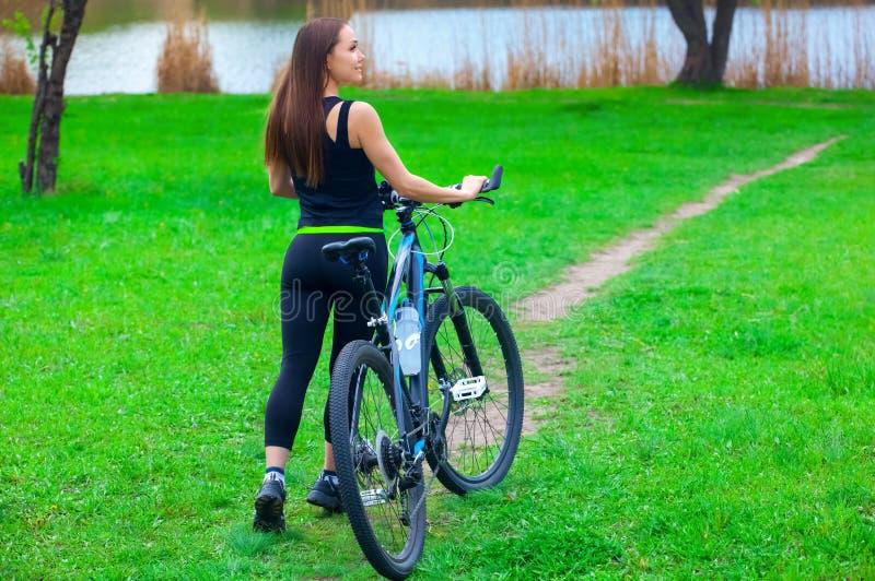 Den härliga kvinnan i svart träningsoverall rider en cykel i morgonen i parkera royaltyfri foto